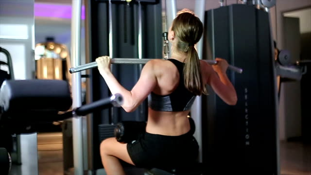 vídeos de stock e filmes b-roll de girl lifting weights on lat machine - braço humano