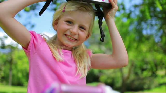 Girl puts on a pink cycling helmet and fastens the clasps