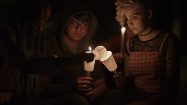 vídeos de stock e filmes b-roll de girl lighting candle of friend at candlelight vigil at night / provo, utah, united states - provo