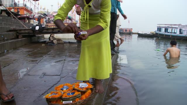 Girl lighting floating candles on riverbank boy bathing in back