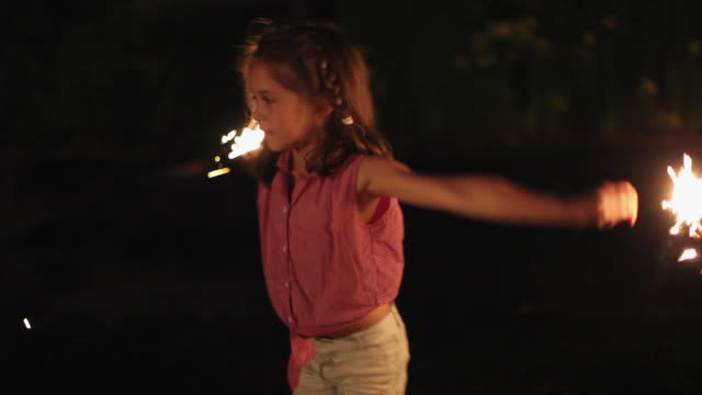 vidéos et rushes de ws pan girl (4-5) lighting sparklers on 4th of july / lovell, maine, usa - cierge magique