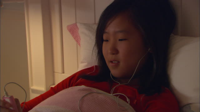 cu, girl (10-11) listening mp3 player in bed - one girl only stock videos and b-roll footage