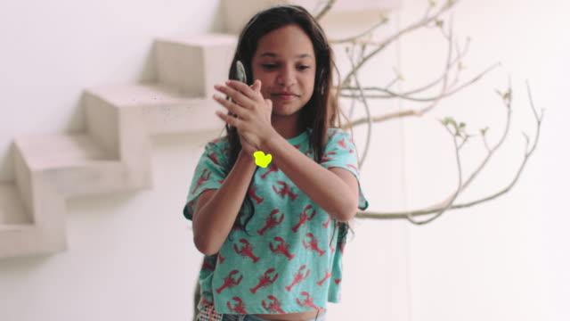 vídeos de stock, filmes e b-roll de girl listening music and dancing to music on headphones with motion responds animation in 4k - miscigenado