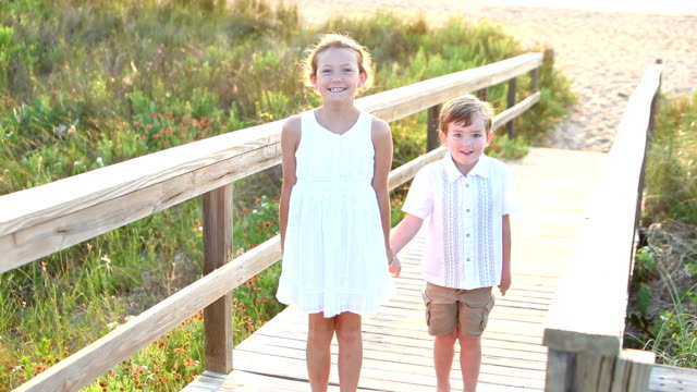girl, little brother at beach running on wooden walkway - family with two children stock videos & royalty-free footage