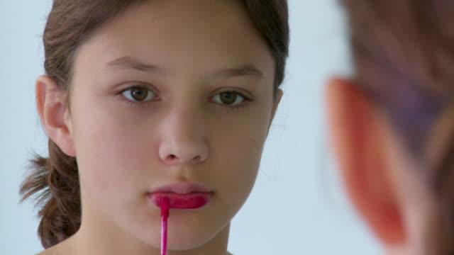 CU, Girl (12-13) looking applying lipstick in front of mirror