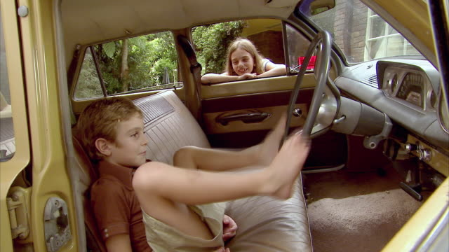 ms, girl (10-11) looking at boy (6-7) and g pretending to drive car with feet, tamborine mountain, brisbane, queensland, australia - pre adolescent child stock videos & royalty-free footage