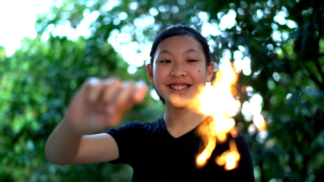 slo mo girl looking at camera and holding sparklers in hand - girls flashing camera stock videos and b-roll footage