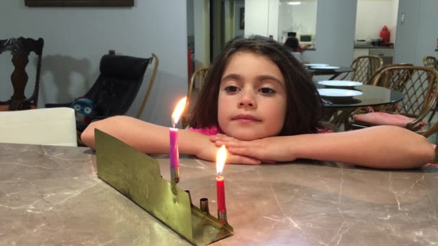 Girl Looking at the First Candles of Chanukah Jewish Holiday on a Menorah