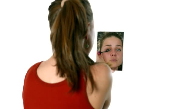girl looking at the mirror and doing her make up applying eyeliner mascara - stage make up stock videos and b-roll footage