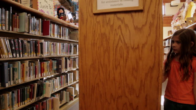 vídeos de stock e filmes b-roll de ws pan girl looking for books walking through bookshelves at library / flagstaff, arizona, usa - soletrar