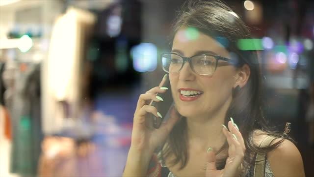 vídeos y material grabado en eventos de stock de chica busca en la ventana de la tienda y hablando con amigo en el teléfono móvil - escaparate de tienda