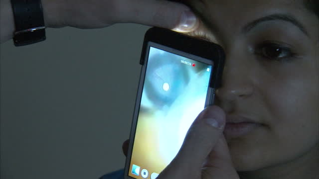 Girl looking in to new smartphone app developed in the UK could revolutionise the way blind or partially sighted peopled are treated in developing...