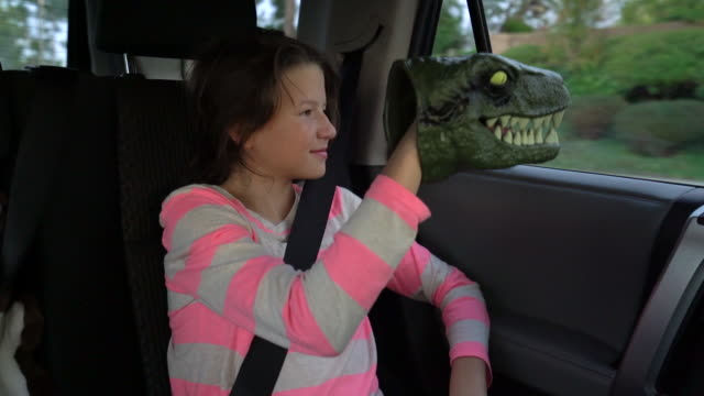 sm ms girl looking out the window of a car playing with her toy dinosaur - ユーラシアエスニシティ点の映像素材/bロール