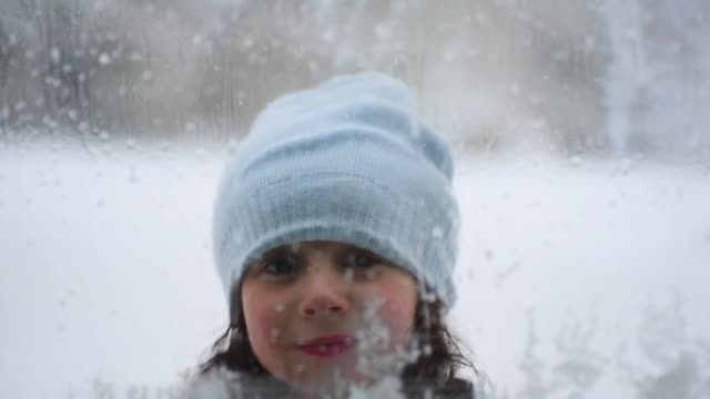 a girl looking through a snowy window. - woolly hat stock videos and b-roll footage