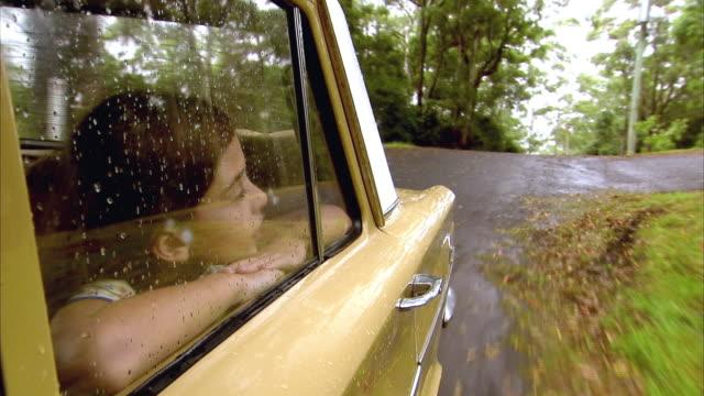 cu, girl (10-11) looking through car window in rain, tamborine mountain, brisbane, queensland, australia - 40 sekunder eller längre bildbanksvideor och videomaterial från bakom kulisserna