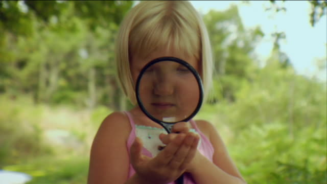 CU Girl looking through magnifying glass at butterfly in her hand / Vinalhaven, Maine, USA