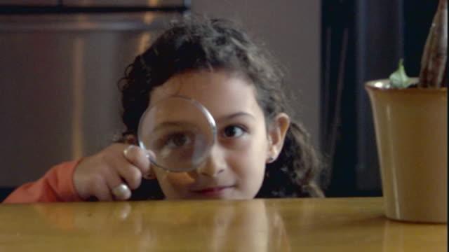 cu girl (8-9) looking through magnifying glass / jersey city, new jersey, usa - vergrößerungsglas stock-videos und b-roll-filmmaterial