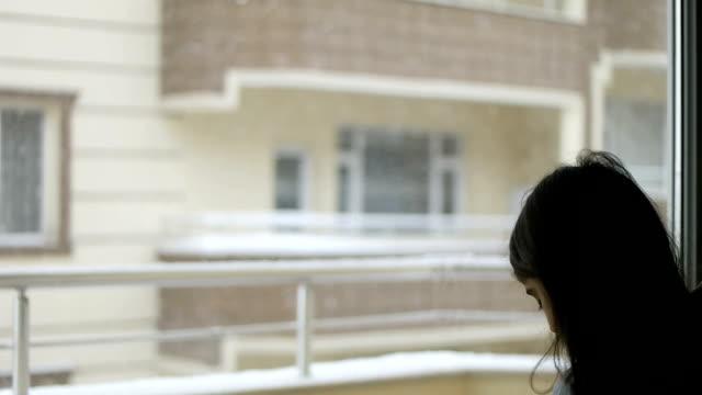 flickan tittar genom snöiga