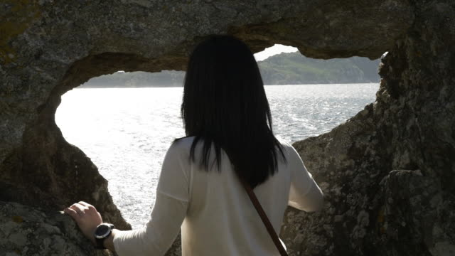 girl looking to the sea trough a hole in the rock - galicia stock videos & royalty-free footage