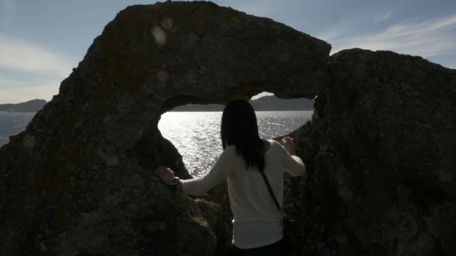 girl looking to the sea trough a rock hole - galicia stock videos & royalty-free footage
