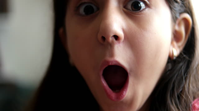 girl looks and is surprised and happy to receive a surprise. - sorpresa video stock e b–roll