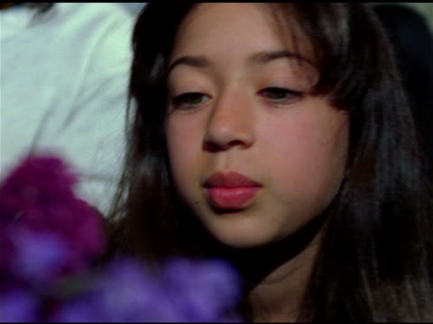 girl looks around thoughtfully, blurred purple flowers in foreground - sideways glance stock videos and b-roll footage