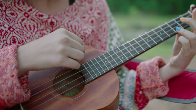 CU SLO MO. Girl looks down and strums ukulele on camping trip with friends.