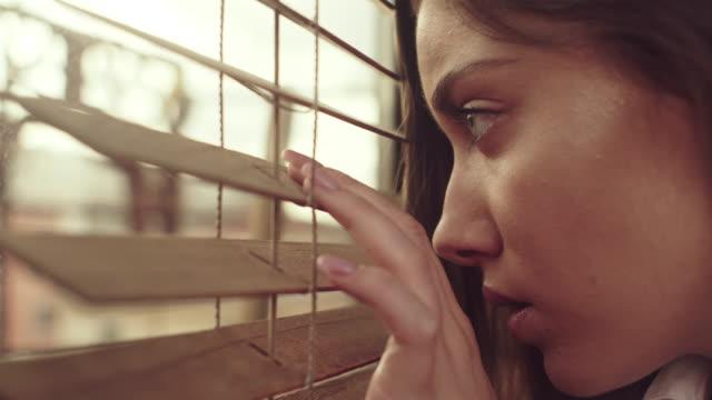 vídeos de stock, filmes e b-roll de garota olha através de cortinas - looking through an object