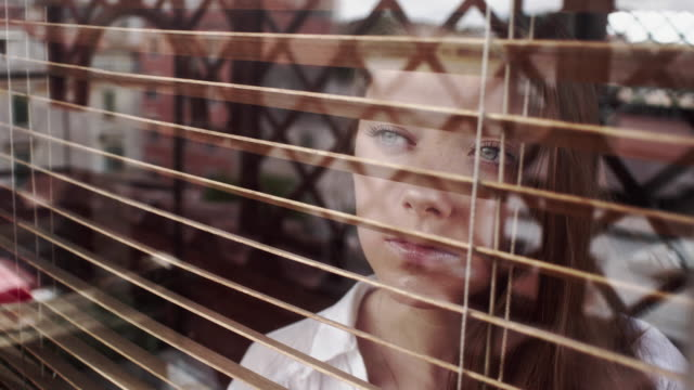 girl looks through blinds - looking through window stock videos & royalty-free footage