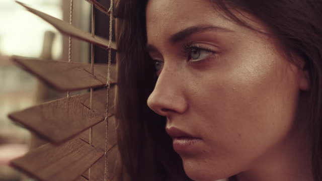 girl looks through blinds - guardare fuori dalla finestra video stock e b–roll