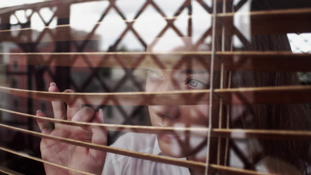 girl looks through blinds - tapparella video stock e b–roll