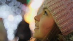 A girl looks up at a Christmas tree while standing in the square
