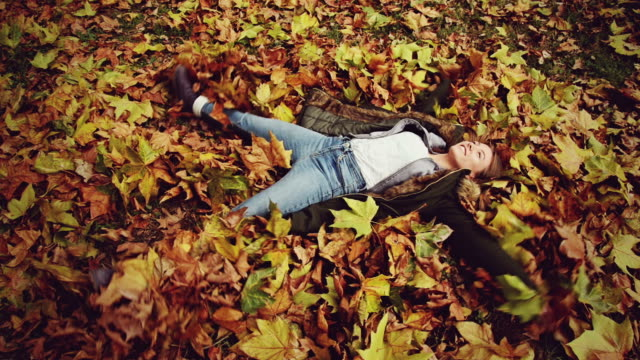 girl lying down on dry leaves - lying on back stock videos and b-roll footage
