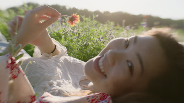 MS SLO MO. Girl lying in green field holding flower turns and smiles at camera.