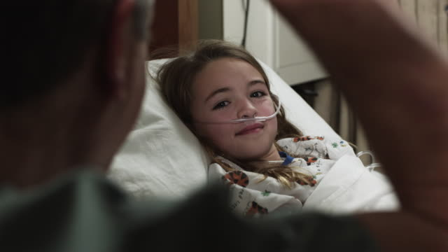 vidéos et rushes de cu girl (8-9) lying in hospital bed being visited / payson, utah, usa - payson