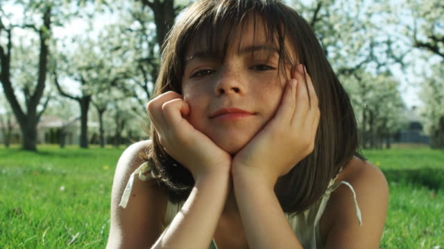 girl lying in the grass - hand am kinn stock-videos und b-roll-filmmaterial