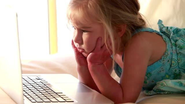 vídeos y material grabado en eventos de stock de cu girl (2-3) lying on bed looking at laptop / lamy, new mexico, usa - mano en la barbilla