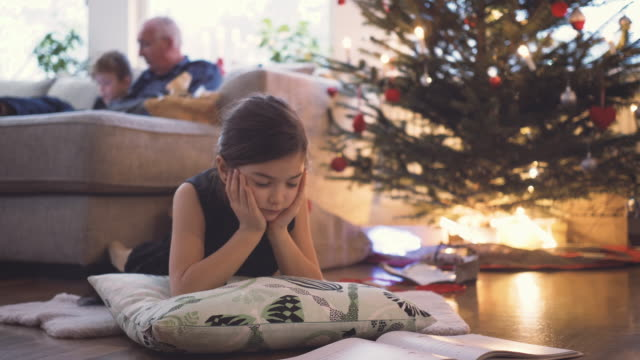 girl lying on floor reading book in front of christmas tree and presents at home - sister stock videos & royalty-free footage