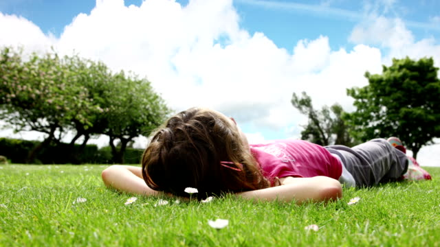 dolly : girl lying on the grass - reclining stock videos & royalty-free footage