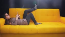 Girl lying relaxing on the couch and scrolling using her smart phone