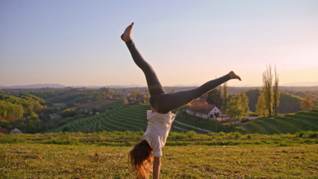 girl makes acrobatic move in grass - farmhouse stock videos & royalty-free footage
