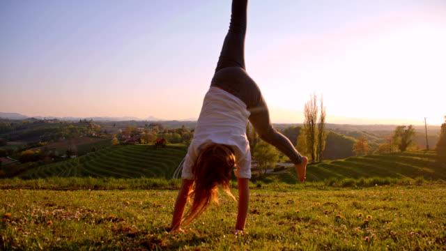 slo mo girl makes cartwheel on the meadow - cartwheel stock videos & royalty-free footage