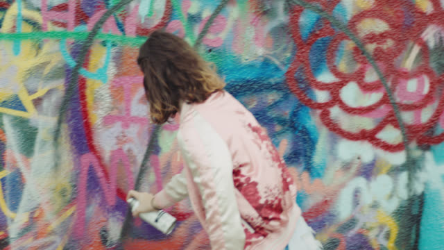 vidéos et rushes de ms. girl makes design with spray paint on graffiti wall. - couleur vive