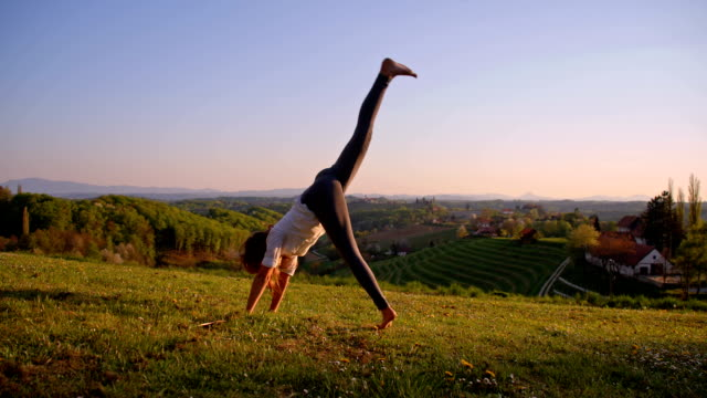 SLO MO Girl makes handstand on the meadow