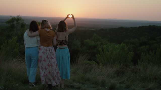 WS SLO MO. Girl makes heart shape with hands framing the setting sun on green mountainside with friends.