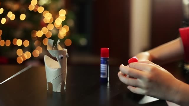girl making a cardboard reindeer with a red nose at her home with christmas lights behind - 30 sekunden oder länger stock-videos und b-roll-filmmaterial