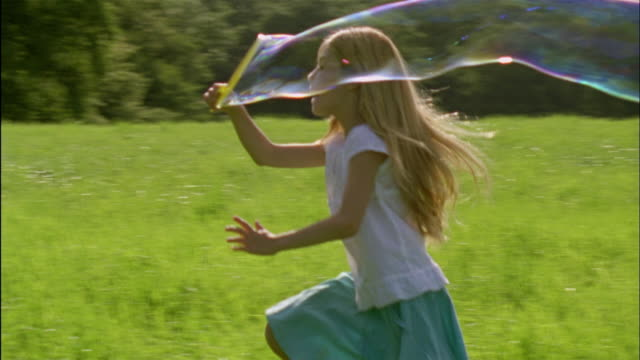 vidéos et rushes de ms, pan, girl (6-7) making bubbles and running through field, chateau du parc, saint ferme, france - cadrage aux genoux