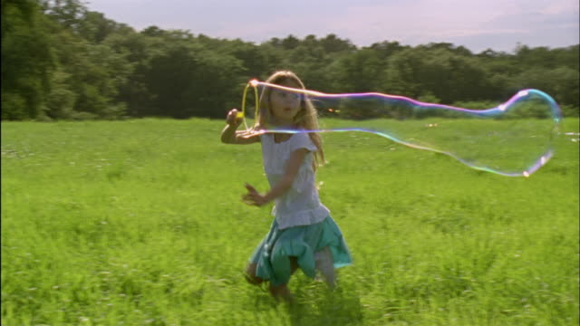 MS, PAN, Girl (6-7) making bubbles and running through field, Chateau du Parc, Saint Ferme, France
