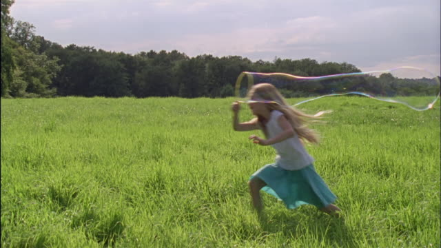 ms, girl (6-7) making bubbles and running through field, chateau du parc, saint ferme, france - one girl only stock videos and b-roll footage