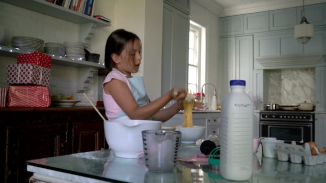 Girl mixing dough with wire whisk during christmas